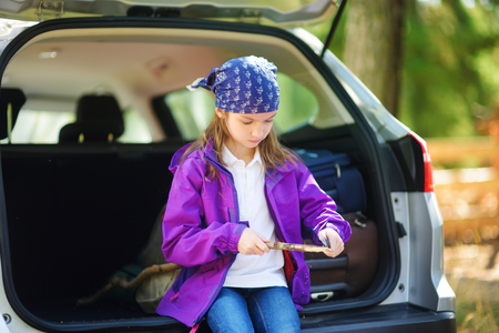 trinchante: Cute little girl sitting in a car and using a pocket knife to whittle a hiking stick. Child using a carving knife. Family car trip with small kids. Foto de archivo
