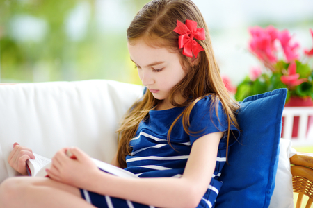 one room school house: Adorable little girl reading a book in white living room on beautiful summer day. Smart schoolgirl doing her homework at home after school.