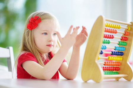 abaco: Cute little girl playing with abacus at home. Smart child learning to count. Preschooler having fun with educational toy at home or kindergarten.