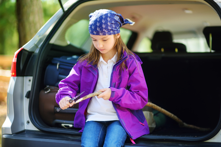 whittle: Cute little girl sitting in a car and using a pocket knife to whittle a hiking stick. Child using a carving knife. Family car trip with small kids. Stock Photo