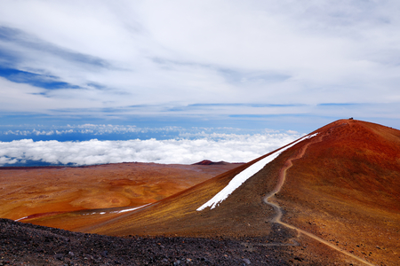 The summit of Mauna Kea, a dormant volcano on the island of Hawaii. Stunningly beautiful red stone peak hovering above clouds, the highest point in the state of Hawaii, USA.