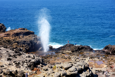 Tourists admiring the Nakalele blowhole on the Maui coastline. A jet of water and air is violently forced out through the hole in the rocks. Hawaii, USA. Stock Photo