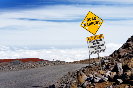 A road sign on a steep road to the summit of Mauna Kea, a dormant volcano on the island of Hawaii. The peak of Mauna Kea peak is the highest point in the state of Hawaii.
