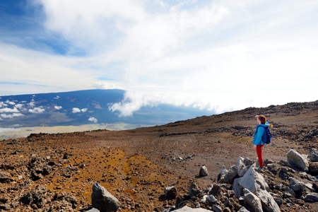 Tourist admiring breathtaking view of Mauna Loa volcano on the Big Island of Hawaii. The largest subaerial volcano in both mass and volume, Mauna Loa has been considered the largest volcano on Earth. Stock Photo
