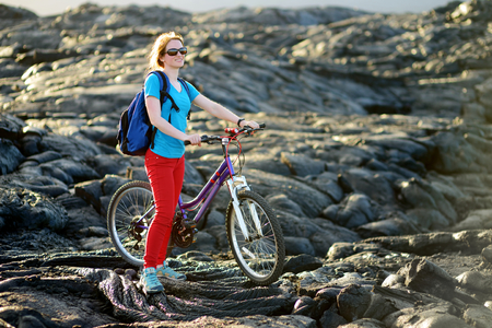 Young tourist cycling on lava field on Hawaii. Female hiker heading to lava viewing area at Kalapana town on her bike. Tourist on hike near Kilauea volcano around Hawaii volcanoes national park, USA. photo