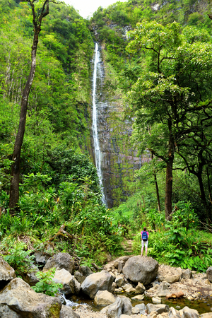 Young female tourist hiking to the famous Waimoku Falls at the head of the Pipiwai Trail, above Seven Sacred Pools on the Road to Hana. Maui, Hawaii, USA. photo