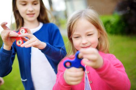 Twee grappige zusters die met kleurrijke fidgetspinners spelen op de speelplaats. Populair stressverlichtend speelgoed voor schoolkinderen en volwassenen. Stockfoto
