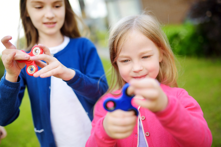 Two funny sisters playing with colorful fidget spinners on the playground. Popular stress-relieving toy for school kids and adults.