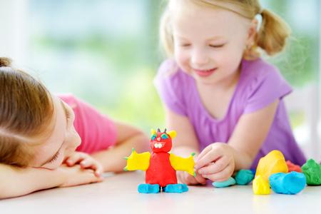 Deux petites s?urs mignon ayant du plaisir ensemble avec la pâte à modeler colorée dans une garderie. enfants Creative moulage à la maison. Les enfants jouent avec de la plasticine ou de la pâte. Banque d'images