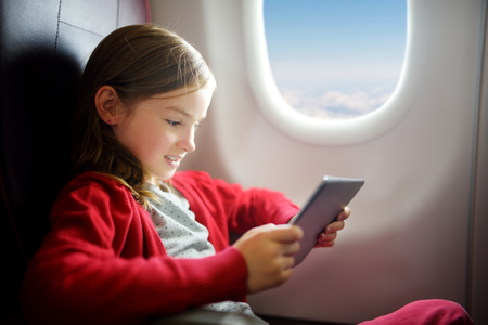 adentro y afuera: Adorable little girl traveling by an airplane. Child sitting by aircraft window and using a digital tablet during the flight. Traveling abroad with kids. Foto de archivo