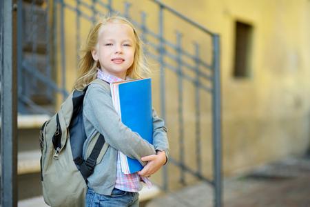 Aanbiddelijk weinig schoolmeisje dat in openlucht op heldere de herfstdag bestudeert. Jonge student die haar thuiswerk doet. Onderwijs voor kleine kinderen. Terug naar school-concept.