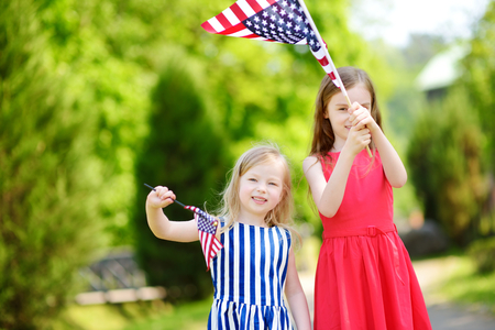 Two adorable little sisters holding american flags outdoors on beautiful summer day. Independence Day concept. Stock Photo