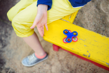 School girl playing with colorful fidget spinner on the playground. Popular stress-relieving toy for school kids and adults.