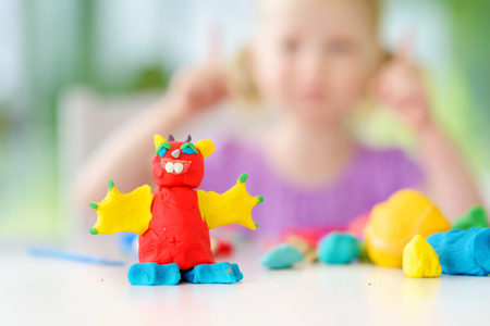 Cute petite fille ayant du plaisir avec la pâte à modeler colorée dans une garderie. Creative moulage par enfant à la maison. Enfant jouer avec de la plasticine ou de la pâte.
