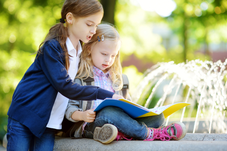 Adorable little schoolgirls studying outdoors on bright autumn day. Young students doing their homework. Education for small kids. Back to school concept