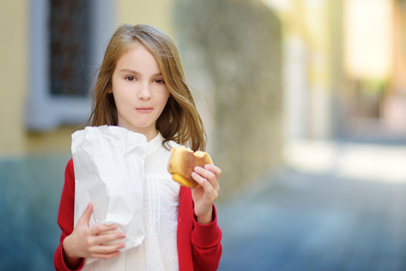 maderno: Adorable little girl eating fresh baked bun on warm and sunny summer day in Toscolano-Maderno town in Italy