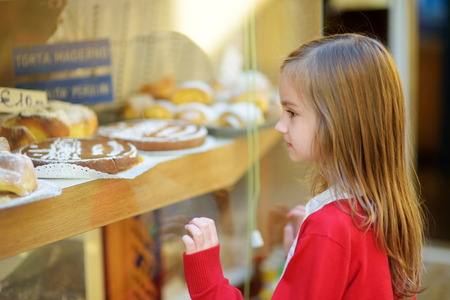maderno: Adorable little girl looking at fresh baked buns on warm and sunny summer day in Toscolano-Maderno town in Italy Stock Photo