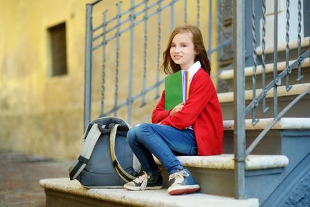 spolužák: Roztomilá školačka studovat venku na světlé podzimní den. Mladý student dělá její úkoly. Vzdělávání pro malé děti. Zpět do školy konceptu. Reklamní fotografie