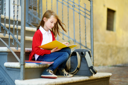 spolužák: Adorable little schoolgirl studying outdoors on bright autumn day. Young student doing her homework. Education for small kids. Back to school concept.