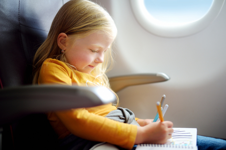 Adorable little girl traveling by an airplane. Child sitting by aircraft window and drawing a picture with colorful felt-tip pens.