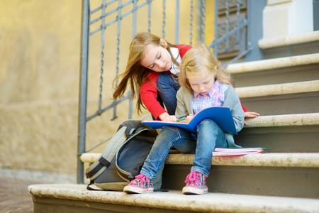 spolužák: Rozkošné malé školáky, které studují venku na jasný podzimní den. Mladí studenti dělají domácí úkoly. Vzdělání pro malé děti. Koncept školy