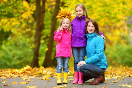Two cute little girls and their mother having fun on beautiful autumn day. Happy children playing in autumn park. Kids gathering yellow fall foliage. Autumn activities for children. photo