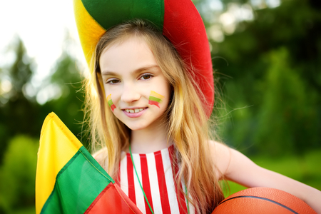 Funny little girl supporting and cheering her national basketball team during basketball championship. Cute Lithuanian team fan.