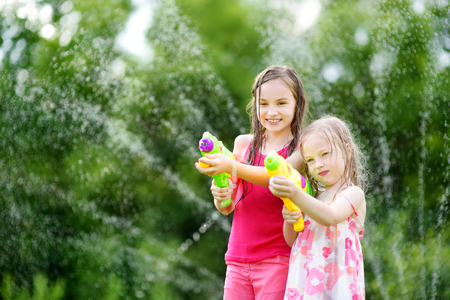 Adorable little girls playing with water guns on hot summer day. Cute children having fun with water outdoors. Funny summer games for kids.