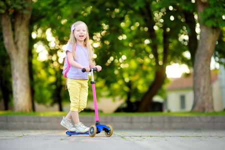 Small child learning to ride a scooter in a city park on sunny summer evening. Cute little girl riding a roller. Active leisure and outdoor sport for kids. Stock Photo