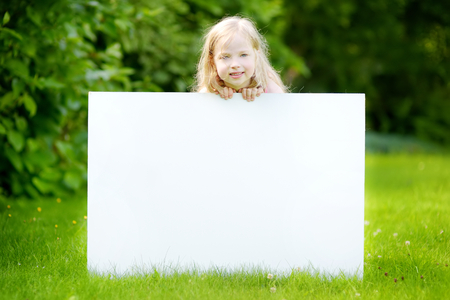 Cute little girl holding big blank whiteboard on warm and sunny summer day outdoors Stock Photo