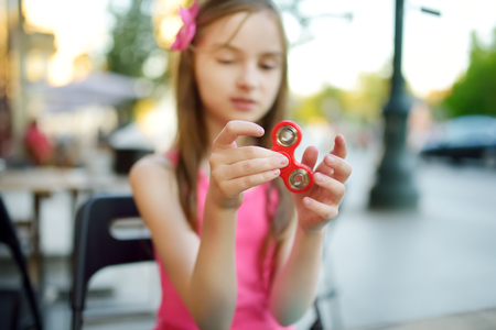 Cute school girl playing with colorful fidget spinner in outdoor cafe. Popular stress-relieving toy for school kids and adults.