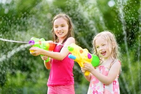 뜨거운 여름 날에 물 총을 가지고 노는 사랑스러운 작은 소녀. 귀여운 어린이 야외 물 재미입니다. 아이들을위한 재미있는 여름 게임.