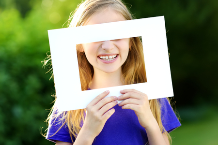 picture framing: Cute cheerful little girl holding white picture frame in front of her face. Adorable child framing her smiling face. Stock Photo