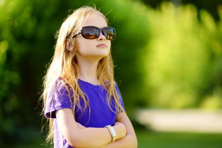 Aanbiddelijk preteen meisje die zonnebril op zonnige de zomerdag in openlucht dragen Stockfoto