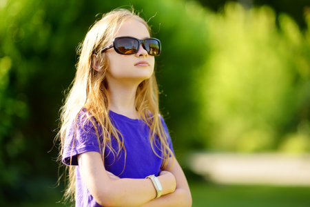 Adorable preteen girl wearing sunglasses on sunny summer day outdoors