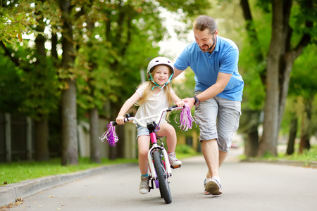Happy father teaching his little daughter to ride a bicycle. Child learning to ride a bike. Family activities at summer.