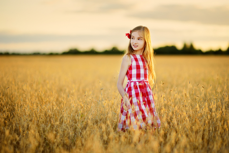 Adorable girl walking happily in wheat field on warm and sunny summer evening. Cute little child in rye field on sunset. Stock Photo