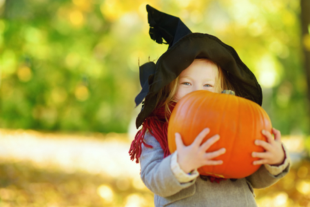 Adorable little girl wearing halloween costume having fun on a pumpkin patch on beautiful autumn day. Happy child playing in autumn park. Autumn activities for children.