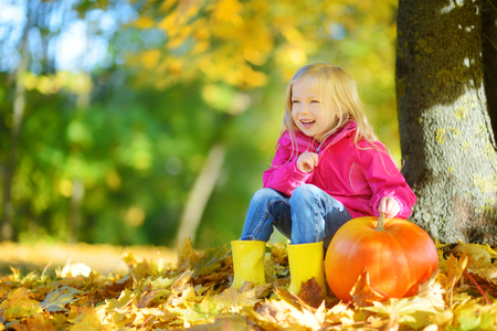 Adorable little girl having fun on a pumpkin patch on beautiful autumn day outdoors. Happy child playing in autumn park. Kid gathering yellow fall foliage. Autumn activities for children.