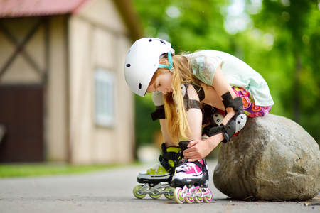 Pretty little girl learning to roller skate on beautiful summer day in a park. Child wearing safety helmet enjoying roller skating ride outdoors. Stock Photo