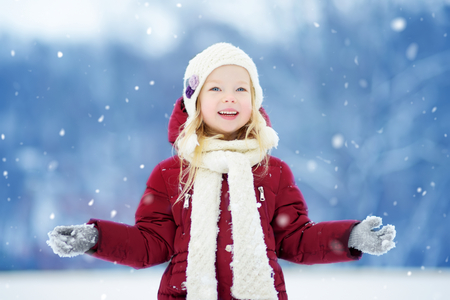 Adorable little girl having fun in beautiful winter park. Cute child playing in a snow. Winter activities for kids. Imagens