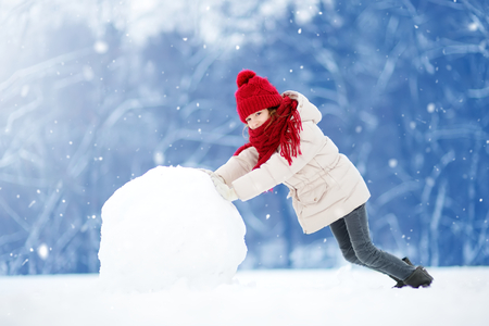 Adorable little girl building a snowman in beautiful winter park. Cute child playing in a snow. Winter activities for kids. Zdjęcie Seryjne - 86040240