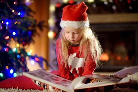 Happy little girl reading a story book by a fireplace in a cozy dark living room on Christmas eve. Celebrating Xmas at home.