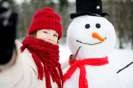 Adorable little girl building a snowman in beautiful winter park. Cute child playing in a snow. Winter activities for kids. Banque d'images