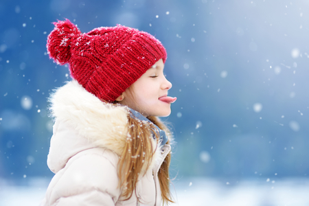 Adorable little girl catching snowflakes with her tongue in beautiful winter park. Cute child playing in a snow. Winter activities for kids. Фото со стока - 89033692