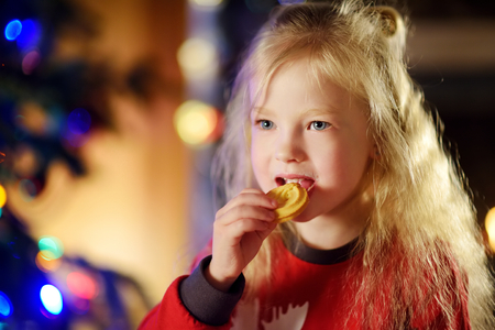 Happy little girl having milk and cookies by a fireplace in a cozy dark living room on Christmas eve. Celebrating Xmas at home. Stock Photo