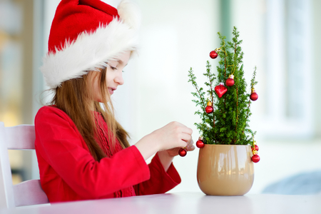 Adorable little girl wearing Santa hat decorating small Christmas tree in a pot on Christmas morning. Celebrating Xmas at home. Stock Photo