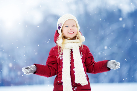 Adorable little girl having fun in beautiful winter park. Cute child playing in a snow. Winter activities for kids. Stock Photo