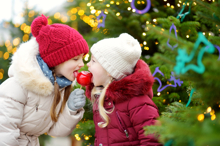 Two adorable little sisters eating red apples covered with sugar icing on traditional Christmas market. Children enjoying sweets, candies and gingerbread on magical Xmas time. Stock Photo