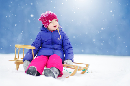 Funny little girl having fun with a sleight in beautiful winter park. Cute child playing in a snow. Winter activities for kids. Stock Photo